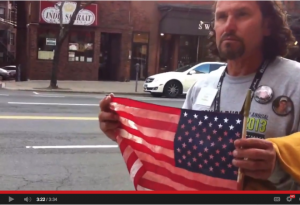 A photo op dreamed up by a PR firm: Carlos displays his blood soaked American flag.